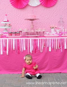 Birthday Girl: One-year-old birthday girl Emmalyn sits in front of a beautiful dessert table, complete with lots of sweets and adorable details, including a ruffle fabric backdrop and poms from Etsy seller Pom Flair and a table with pink fabric and a ribbon garland from Etsy's A To Zebra Celebrations.