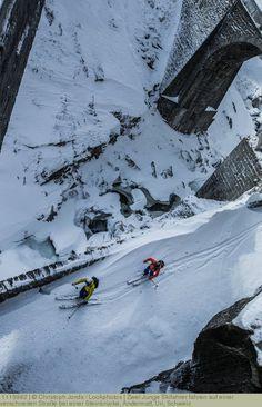Zwei Junge Skifahrer fahren auf einer verschneiten Straße bei einer Steinbrücke, Andermatt, Uri, Schweiz Andermatt, Winter Sports, Switzerland, Mount Everest, Skiing, Mountains, Nature, Skiers, Guys