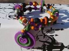 Button accented bracelet for the seamtress in your life, orange, purple, green and black memory wire bracelet with button accents