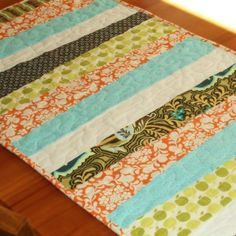 cue scrappy strips table runner - could make placemats instead to practice free motion quilting.