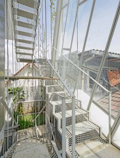 White mesh stairs with opague treads connect three floors of a slanted house in Indonesia