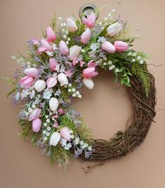 """This pretty handmade wreath measures 18"""" tall x 16"""" wide x 5"""" deep and is made on a 14"""" grapevine base. There are a variety of light and dark pink tulips, purple filler flowers and lily of the valley. 