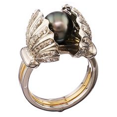 Shy Black Pearl Ring! _ Here's a beautiful black pearl ring called Shy Pearl Ring.  I really like how the black pearl shines the whole ring, definitely a recommended buy.  (might even be good enough for engagement rings). Encrusted with eighty-two sparkling white diamonds, this ring is truly a gem with a magical secret. Three eighteen karat gold rings pivot to reveal a hidden treasure within the shell – a single black pearl one would never expect.