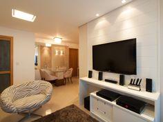 O home theater foi adaptado na sala de estar deste apartamento em Salvador (BA). Móvel sob medida em mdf branco com gavetas e porta de correr fazem parte do projeto de marcenaria. Tons neutros, como branco e bege, incluem a paleta de cores deste espaço de 4,8 x 3,0 m. O projeto é da arquiteta Maristela Bernal.
