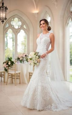 A style both modern and feminine, this lace wedding dress from Stella York brings all your romantic wedding-day dreams to life! With its on-trend high neckline, this stunning style features sheer, graphic lace and a plunging sweetheart neckline, giving you the best of both worlds. The graphic lace pattern continues throughout the gown, hugging your curves before flaring out into a mermaid silhouette, complete with a scalloped hemline. Sheer, lace side cutouts add an element of sexiness to…