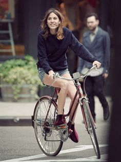 Alexa Chung riding her bicycle after lunch with few female friends in SoHo, New York City 14 May 2012. Navy sweater + denim shorts + red velvet boots