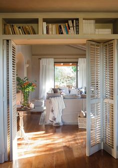Living Room, bookcases, shutters dividing rooms, wood floors, white furnishings,