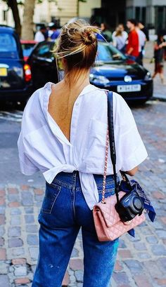 Pink Chanel quilted purse, high-waisted denim, white button-down tied and reversed