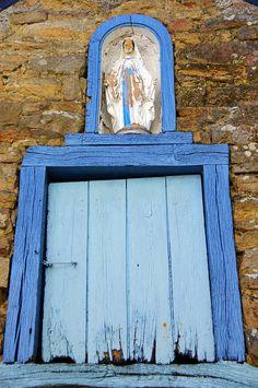 Une fenêtre en bois bleu surmontée d'une petite niche avec la statue de la Vierge Marie. A Baden, joli petit bourg du Golfe du Morbihan entre Vannes et Auray.