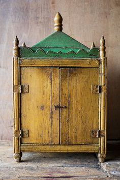 Stow away your most precious treasures in this Vintage Green and Yellow Painted Shrine. Great for your yoga studio or meditation space. With scalloped edges and hidden details, this antique cabinet is