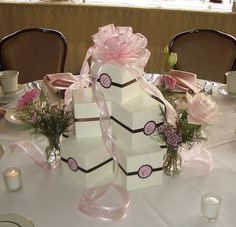 Wedding cupcake box arrangement by sgodlove, via Flickr - Cupcake favors presented in an Italian embossed boxes with ribbon and personalized label. Used 8 at each table as part of centerpiece with flowers and cascading ribbons.