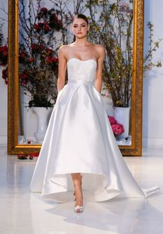 Strapless high-low gown of Mikado with beaded lace appliqués on bodice and skirt with pockets