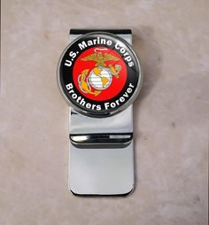 Brothers Forever USMC Money Clip. Welcome Up for sale is this beautiful money clip. The metal portion is composed of brass and weighs approximately 17 grams.Central Round Image: 25 mm in diameter, (approximately 1 inch). The rectangular clip portion is 55 mm in length and 22 mm wide The setting encompasses a high resolution image that has been printed with a printer specifically made for printing high resolution images. The image is sealed with a high quality resin to ensure vibrancy and...