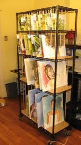 art storage racks - ooooh... great idea!  generic storage shelves with DIY art separators.  So much cheaper than buying a storage rack made specifically for art.