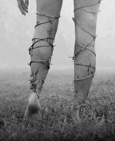 Exhausted, wrapped in barbed wire, she staggers through the field.