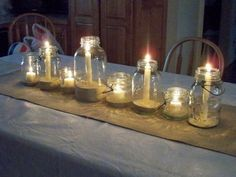 A beautifully and simply set reception table shines warmly with vintage canning jars and white candles of varying sizes.