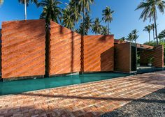 This stripy brick home stands among coconut trees on the shoreline of Ko Pha Ngan, an island in the Gulf of Thailand.