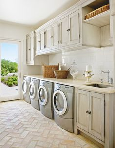 The Refined Group opted for whitewashed chevron brick floors in this laundry room.