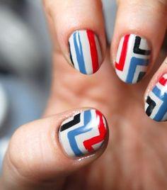 Nail art con rayas azules, negro y rojo