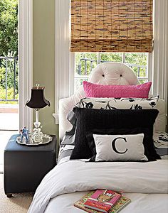 upholstered tufted headboard with contrasting buttons, sage green walls, heavy molding, black and white linens with monogrammed pillow, hot pink pillow, black cube with nail head trim, silver tray, crystal lamp with black silk shade, bamboo shade - perfect teen room or guest room bed - from House Beautiful