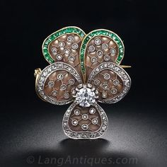 Gorgeous Plique-a-Jour Diamond and Emerald Pansy Brooch - 50-1-2837 - Lang Antiques. An enchanting Art Nouveau pansy pin featuring shimmering Plique-a-Jour (translucent) enamel petals which effectively emulates the look of frosted crystal. Superb calibre emeralds and twinkling rose-cut diamonds outline the five petals and tiny rose-cuts also dot the platinum lattice work inside. A .55 carat European-cut diamond beams from the center of the this fabulous bejeweled flower, finely crafted in…