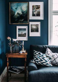 Deco ton sur ton bleu sur bleu dans ce salon au mur bleu foncé aux photos bleu canard et au canapé bleu jeans !