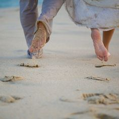 Leaving their footprints in the sand, heading towards the ocean, barefoot wedding...