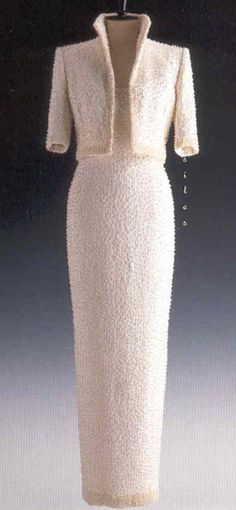 Designed by Catherine Walker, this white silk-crepe sheath dress and matching high-collared jacket is embroidered all over with simulated pearls and white sequins. Diana debuted the gown at The British Fashion Awards on October 17, 1989. She wore it again on November 8, 1989 to the opening of the Hong Kong Cultural Center. The princess also wore it without the jacket on May 7, 1990 on a state visit to Hungary. This gown is lot #78 and it raised $ 151,000 for Diana's charities.