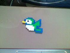 Un pájaro verde,azul,blanco y amarillo.