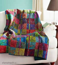 Batiks in rich jewel tones make this throw-size quilt dance with color. Once  individual blocks are completed, the quilt is assembled in vertical rows to  ensure that the narrow pieces line up correctly.