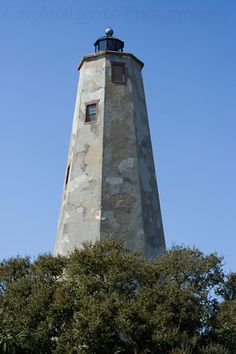 """Bald Head Island Lighthouse was built in 1817. """"It was decided to place a lighthouse on Bald Head Island to guide ships through the channels and sand bars of the Cape Fear River. In addition, one was also needed to help vessels avoid the treacherous Frying Pan Shoals, which extends over 20 miles out into the Atlantic Ocean."""""""