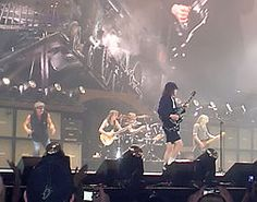 Rock band in performance on a well-lit but hazy stage. At the back is a guitarist; there are two more guitarists, a vocalist off to one side, and a drummer in the rear.  AC/DC