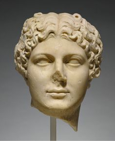 Roman marble head of Agrippina the Younger, 50 A.D. Portraits of Agrippina were produced during the reigns of the emperors Caligula, Claudius, and Nero, the women retain an ageless, classicizing style enlivened by elaborate coiffures. Agrippina is distinguished by her narrow face, dimpled chin, and protruding upper lip, she wears her hair parted in the middle and pulled back, with tight curls surrounding her face, 32 cm high. Getty museum