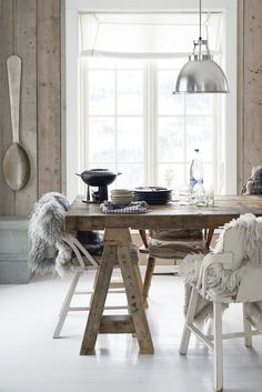 = sawhorse table, furs, industrial lamp and hung spoon