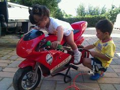 """If only everyone could have children this cool. The little lady is on the bike while the boy fixes it, how gentlemanly."""