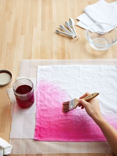Cut a piece of wax paper larger than the napkin and lay it on a work surface. Place the napkin on top with the wet end at the bottom. Using the paintbrush, apply pink dye along the wet edge of the napkin.