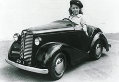 some lucky kid in her roadster pedal car; vintage photo