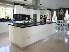A kitchen of contrasts holds this large island in black and white, replete with expansive built-in storage and full range.