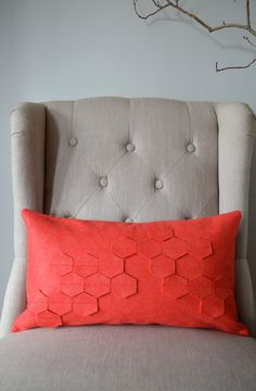 Coral pillow on a grey chair