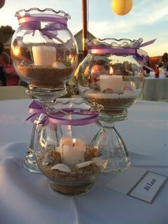 3 tier ivy bowls.  (Hubby had the idea of hot gluing them onto sundae glasses to make them more stable.) Light purple ribbon on dark purple wider ribbon.  Sand and shells inside with citronella candles inside.  (The bride requested citronella candles to keep away the bugs.)