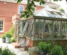 This is a square conservatory with a pyramid roof which replaced a rotting timber structure. Its subtle colour helps it blend beautifully with the house and garden.  www.alitex.co.uk