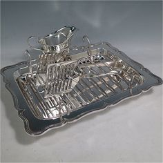 An Antique Edwardian Silver Plated asparagus serving set, having a plain rectangular body, with an applied and shaped reeded border, a wire-work serving rack, a sauce boat sat in a frame with loop handle, a pair of asparagus server tongs, and all sitting on a base with four button feet. All pieces were made by the Atkins Brothers of Sheffield in ca. 1900. The dimensions of this fine hand-made silver-plated asparagus serving set are length 29 cms (11.5 inches), and width, 23 cms (9 inches).