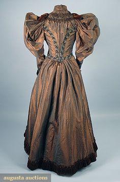 IRIDESCENT SILK DAY DRESS, 1895 2-piece, bronze brocade shot silk w/ huge mutton sleeve & rust velvet trim & green carnival glass bead trim