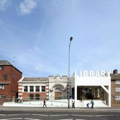 Thornton Heath library in Croydon.The extension just completed by FAT - a white box with LIBRARY in supergraphics across the top,the ostensible modernism subverted by an incongruous support