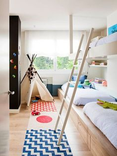 Skandinavisch Kinderzimmer by A! Emotional living & work | Diese schöne Einbaulösung macht es möglich, dass in einem relativ engen Raum drei Leute komfortabel schlafen können. Und dabei handelt es sich nicht bloß um ein Etagenbett – am hinteren Ende ist es mit Bücherregalen ausgestattet und unten gibt es Schubladen, die viel Kram aufnehmen können. Indem das Material für das Bett auf die Farbe des Fußbodens abgestimmt wurde, bekommt der Raum einen sehr einheitlichen Look.