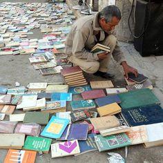 Un uomo vende dei libri su al-Mutanabi Street, nel centro di Baghdad