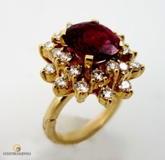 Lively 3.04 oval ruby surrounded by over 1ct of round brilliant cut diamonds set in 18kt yellowgold.