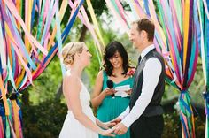wedding arch decorated with brightly colored ribbons