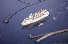 Ein Kreuzfahrtschiff verlässt den Hafen Rostock und befindet sich dabei zwischen West- und Ostmole des Ostseebades Rostock-Warnemünde. Aus d...
