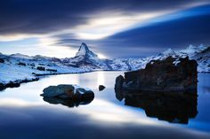 Matterhorn by Tobias Richter taken on a cold evening in October conveys a mystic atmosphere. After the first snowfall, the Stelli Lake is slightly snow-covered but still ice-free. The long exposure captures the moving clouds above the mountain tops of the Valais Alps.  Equipment: Canon 5d II, Canon 16-35 II, Lee Big Stopper
